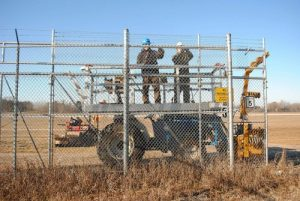 Crew members attach fabric to the fence at the gate entrance.