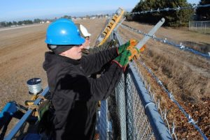 A crew member hooks the barbed wire in a barb arm.