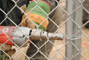 Crew member attaches chain link fabric to a fence post with an Easy Twist Tie.