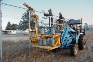 A blue tractor dispenses barbed wire on a chain link fence