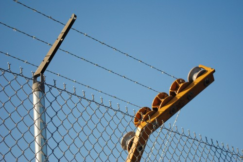 a machine dispenses barbed wire to chain link fence