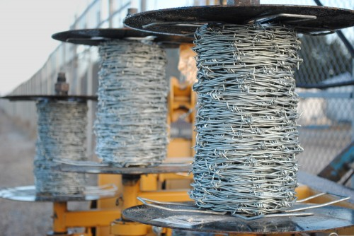 spools of barbed wire are loaded on a barbed wire dispenser