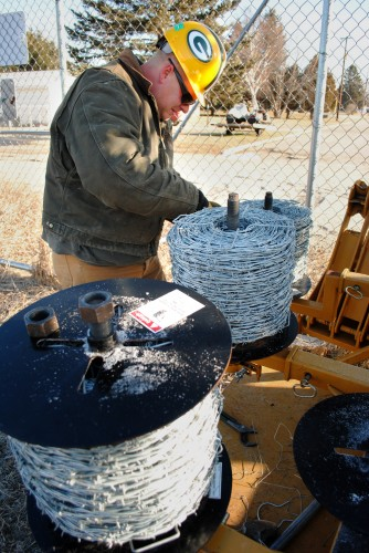 worker loads barbed wire onto a barbed wire dispenser
