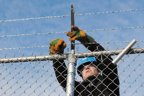 worker installs barbed wire onto a chain link fence