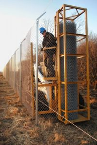 Installink stretches chain link fabric on a barbed wire fence