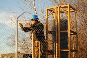 Installink installs chain link fabric on a barbed wire fence