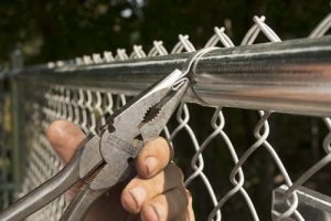 To install a Self-Locking Fabric Band, pinch the ends together with fence pliers and bend down.