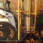 Installink stretches wire chain link fabric using a skid steer
